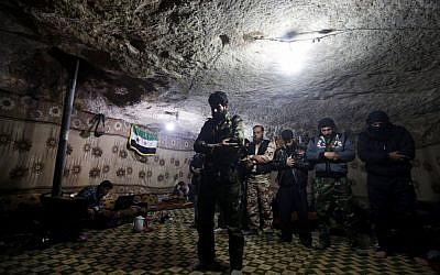 Free Syrian Army fighters pray inside a cave at Jabal al-Zaweya in Idlib, Syria, Sunday Feb. 24, 2013 (photo credit: AP/Hussein Malla)