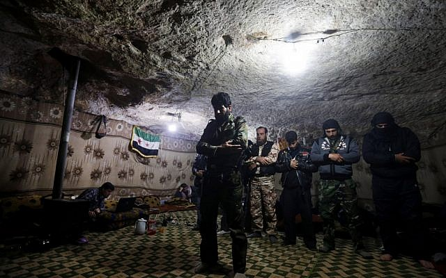 Free Syrian Army fighters pray inside a cave at Jabal al-Zaweya in Idlib, Syria, Sunday Feb. 24, 2013 (photo credit: AP/Hussein Malla)