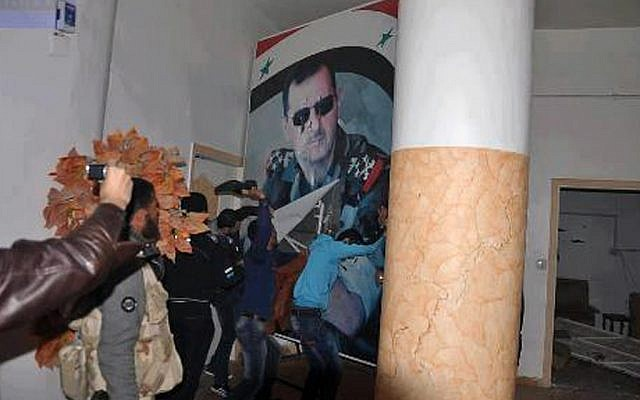 Citizen journalism image provided by Coordination Committee in Kafr Susa which has been authenticated based on its contents and other AP reporting, shows people tearing down a huge poster of President Bashar Assad and hitting it with their shoes, in Raqqa, Syria, Monday, March. 4, 2013. The activists said the picture was taken inside the Air Force Intelligence headquarters in Raqqa. (photo credit: AP/Coordination Committee In Kafr Susa)