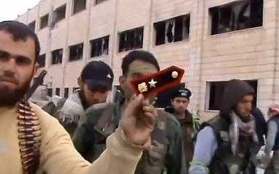In this Sunday March 3, 2013 image taken from video obtained from the Shaam News Network, which has been authenticated based on its contents and other AP reporting, a Syrian rebel fighters displays an epaulette from a government soldier during a tour of the police academy complex in Khan al-Asal, in the province of Aleppo, Syria. (photo credit: AP/Shaam News Network via AP video)
