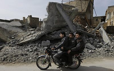 A Syrian drives his motorbike past a house destroyed in a government airstrike, at Jabal al-Zaweya village of Sarjeh, in Idlib, Syria, Monday February 25, 2013 (photo credit: AP/Hussein Mallah)