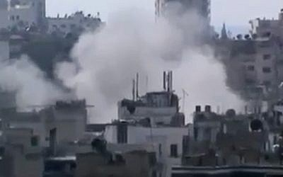 Smoke rises from buildings due heavy shelling in Homs, Syria, on Monday, March 11, 2013. (photo credit: AP Photo/Shaam News Network via AP video)