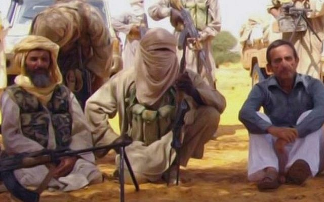 This image taken from video shows a foreign hostage who was among seven seized in Niger in 2010 by al-Qaeda in the Islamic Maghreb. Seated on the left is Abou Zeid (photo credit: AP/SITE)