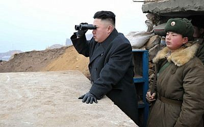 North Korean leader Kim Jong Un uses binoculars to view South Korean territory from an observation post on Jangjae Islet, in March 2013. (photo credit: AP/KCNA via KNS)
