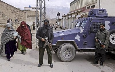 Pakistani security men stand alert as women from Pakistani Hazara Shi'ite community walk past during Friday prayers outside a Shi'ite mosque in Quetta, Pakistan. (AP Photo/Arshad Butt)