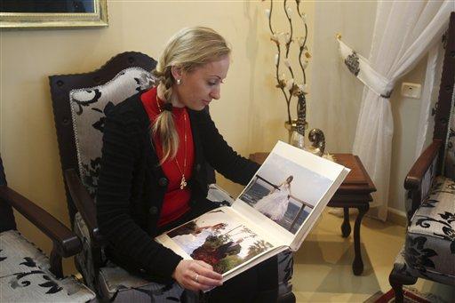 Ukrainian Alla Evdokimova, 26, who now goes by name Alaa Altif, displays her wedding album at her home at Mount Gerizim,  Feb. 20, 2013 (photo credit: AP Photo/Nasser Ishtayeh)