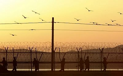 South Korean army soldiers patrol along a barbed-wire fence near the border village of Panmunjom in Paju, South Korea, on Tuesday evening, March 26, 2013. (photo credit: AP Photo/Ahn Young-joon)
