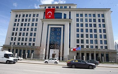 A Turkish flag is hung from the headquarters of Turkish Prime Minister Recep Tayyip Erdogan's ruling party in Ankara, Turkey, Wednesday, March 20, 2013, apparently to conceal the damage after assailants fired a rocket on the building. (photo credit: AP)