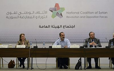 Head of the Syrian National Coalition for Opposition Mouaz al-Khatib, second left, speaks with other unidentified members, during a meeting, March 2013. (photo credit:AP)