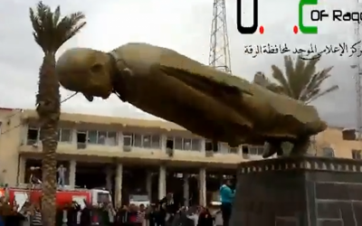 Residents of Raqqa topple a statue of Syrian President Bashar Assad's father and predecessor, Hafez Assad, on Monday, February 4, 2013. (photo credit: image capture from YouTube video)