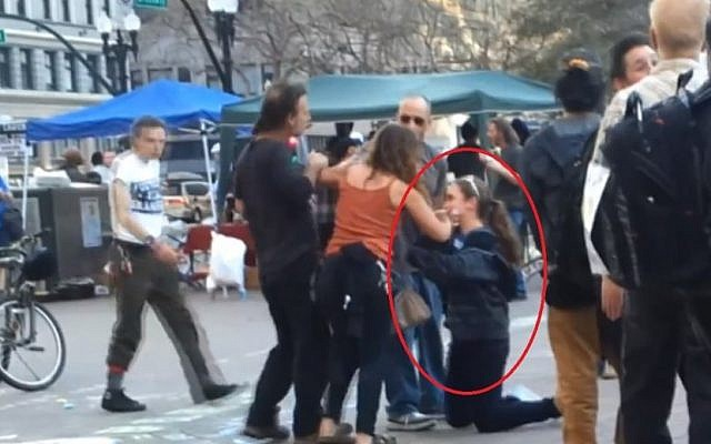 Hannah Larson (on her knees) attacked by pro-Palestinian activists in Oakland (photo credit: screen capture Alba5431/Youtube)