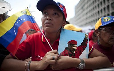 A woman holds a picture of Venezuela's President Hugo Chavez and the country's national flag in Caracas, Venezuela last Wednesday. (photo credit: AP/Ariana Cubillos)
