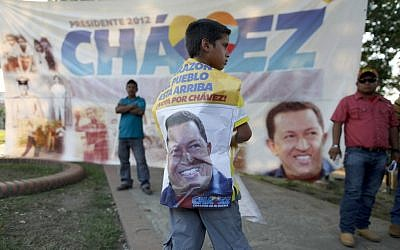 A boy stands in front of a banner of late President Hugo Chavez at the main square of his hometown, Sabaneta, in western Venezuela, Friday. (photo credit: AP/Esteban Felix)