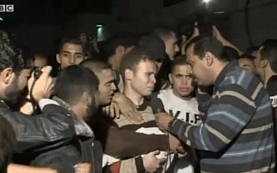 Jihad Mishrawi speaks to the media, while carrying the body of his son Omar, on November 15, 2012. (photo credit: screenshot BBC)