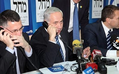 Then-minister of education Gideon Sa'ar (left) and then-minister of environment Gilad Erdan (right) flank Prime Minister Benjamin Netanyahu as they make calls to potential voters ahead of national elections, in Tel Aviv, January 17, 2013. (Gideon Markowicz/ Flash90)