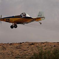 A crop-dusting plane sprays a field in Israel's Negev Desert, Wednesday (Dror Garti/Flash90)