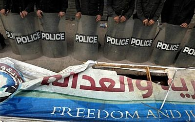 Egyptian anti-riot soldiers stand guard in front of a destroyed banner of the Muslim Brotherhood's Freedom and Justice Party in Cairo, Egypt, Friday, March 22, 2013. (photo credit: AP/Amr Nabil)