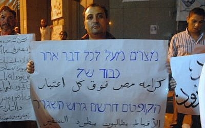 A Coptic protester holding a sign outside the Israeli Embassy in Beirut in 2011. (photo credit: CC BY lilianwagdy, Flickr)
