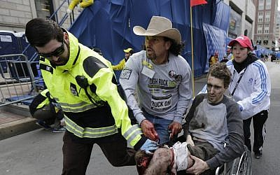 An emergency responder and volunteers -- including Carlos Arredondo, in the cowboy hat -- push Jeff Bauman in a wheelchair after he was injured in an explosion near the finish line of the Boston Marathon, Monday, March 15, 2013. (AP/Charles Krupa, File)