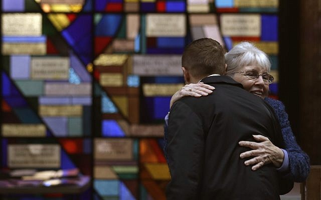 Sue Haff, right, a member of Trinity Episcopal Church in Boston, greets a man arriving at Temple Israel, which allowed the Trinity congregation to hold services on Sunday. (photo credit: AP/Julio Cortez)