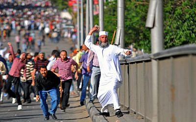 An Egyptian man throws a stone during clashes between rival groups of protesters in Cairo, Egypt, Friday, April 19, 2013. (photo credit: AP/Mostafa Darwish)