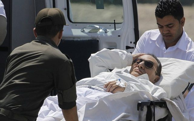 Egyptian medics and army personnel carry former Egyptian president Hosni Mubarak, 84, from a helicopter ambulance after it lands in Maadi Military Hospital following his adjourned trial in Cairo, Egypt, Saturday, April 13, 2013. Egypt's highest court in January ordered a retrial for Mubarak for failing to stop the killing of 900 protestors in the 2011 unrest that ousted him, after accepting an appeal against his life sentence, citing procedural failings. (AP Photo/Amr Nabil)