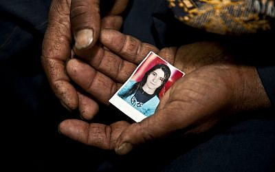 Christian farmer Ishaq Aziz cradles a picture of his daughter, 17-year-old schoolgirl, Nirmeen, who went missing on Valentine's Day and had not been seen or heard of since, in the Minya town of Matai, Egypt, March 27, 2013. (photo credit: AP/Thomas Hartwell)
