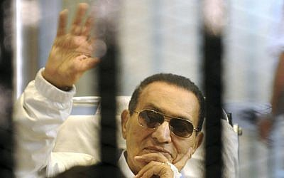 Former Egyptian President Hosni Mubarak waves to his supporters from behind bars as he attends a hearing in his retrial on appeal in Cairo, Egypt, Saturday, April 13, 2013 (photo credit: AP)
