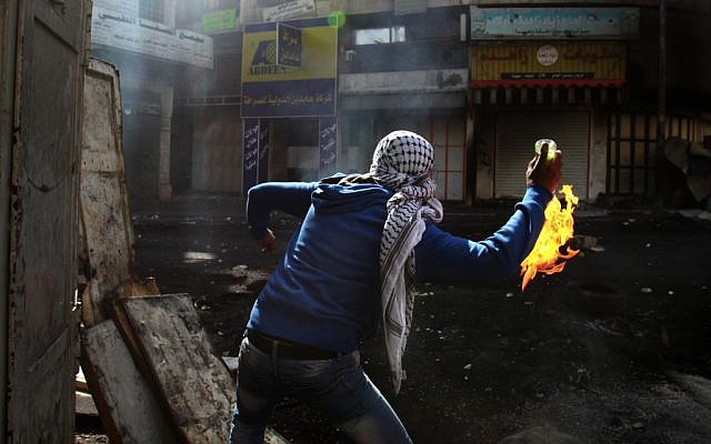 Illustrative photo of a young Palestinian hurling a firebomb in Hebron. (AP/Nasser Shiyoukhi)