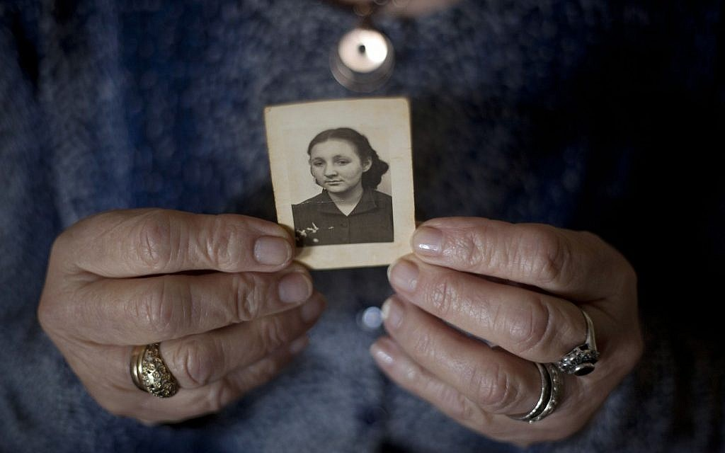 In this April 4, 2013 photo, Warsaw Ghetto Holocaust survivor Aliza Vitis-Shomron, nee Mendel, holds a photograph of herself when she was about 17 years old as she sits in her living room in Kibbutz Givat Oz, Israel. (AP/Ariel Schalit)