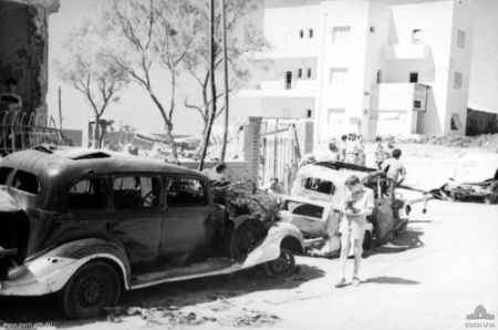 A local civilian carrying his small dog (right) inspects the damage to one of the vehicles as a result of a bombing of Tel Aviv in September 1940. (photo credit: Wikimedia Commons/Nirvi)