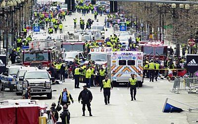 Police clear the area at the finish line of the 2013 Boston Marathon as medical workers help injured following explosions in Boston, Monday, April 15, 2013 (photo credit: AP/Charles Krupa)