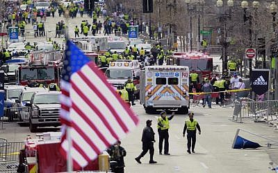 Emergency workers aid injured people at the finish line of the 2013 Boston Marathon following an explosion in Boston, Monday, April 15, 2013. (photo credit: AP/Charles Krupa)