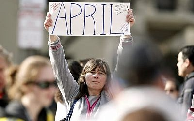 Justine Franco of Montpelier, Vt., holds up a sign near Copley Square in Boston looking for her missing friend, April, who was running in her first Boston Marathon Monday, April 15, 2013. Two bombs exploded near the finish line of the marathon on Monday, killing at least two people and injuring at least 23 others. (photo credit: AP/Winslow Townson)