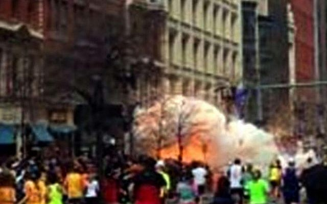 In this image from video provided by WBZ TV, spectators and participants run from the twin explosions that shook the finish line of the 2013 Boston Marathon. (Photo credit: AP/WBZTV)