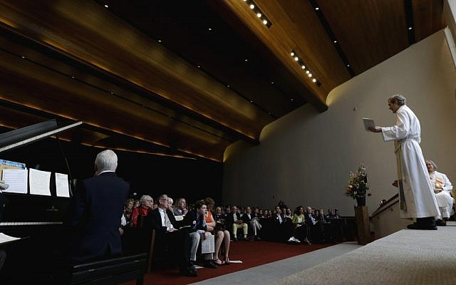 Rev. Samuel Lloyd III, of Trinity Episcopal Church in Boston, leads service at Temple Israel, which allowed the Trinity congregation to hold their service on Sunday. (photo credit: AP/Julio Cortez)