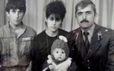 In this image taken from a video, an undated family photo provided by Patimat Suleimanova, the aunt of USA Boston bomb suspects, shows Anzor Tsarnaev left, Zubeidat Tsarnaev holding Tamerlan Tsarnaev and Anzor's brother Mukhammad Tsarnaev. Now known as the angry and grieving mother of the Boston Marathon bombing suspects, Zubeidat Tsarnaev is drawing increased attention after federal officials say Russian authorities intercepted her phone calls, including one in which she vaguely discussed jihad with her elder son. In another, she was recorded talking to someone in southern Russia who is under FBI investigation in an unrelated case, US officials said. (photo credit: AP/Patimat Suleimanova)