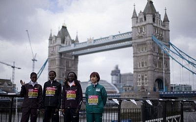 Runners pose for photographs during a media opportunity for the London Marathon back-dropped by Tower Bridge in London, Thursday, April 18, 2013. (photo credit: AP/Matt Dunham)