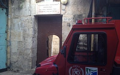 An Israeli fire vehicle parked outside the entrance to the Church of St. John the Baptist, lightly damaged in a small blaze overnight (photo credit: Matti Friedman/Times of Israel)