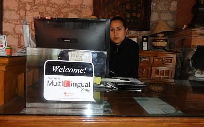 "A woman at a hotel reception desk in Mexico uses the Lexifone app to speak to clients from abroad, hearing the conversation in Spanish, regardless of the language spoken by the other party. ""Mexico is now a Multi-Lingual Zone, thanks to Lexifone,"" said Itay Sagie, the company's director of marketing (Photo credit: Courtesy)"