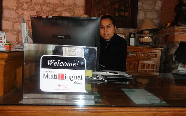 A woman at a hotel reception desk in Mexico uses the Lexifone app to speak to clients from abroad (Photo credit: Courtesy)