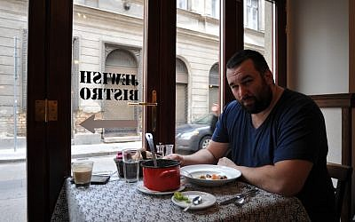 David Popovits, owner of the Matzah Soldier, sits down for a meal at his upscale restaurant in Budapest, March 2013. (photo credit: Cnaan Liphshiz/JTA)