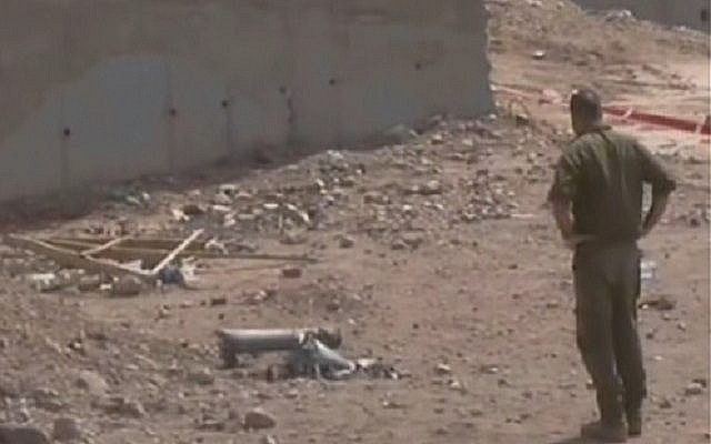 An IDF soldier looks at the remains of a Grad rocket fired on the southern city of Eilat. (photo credit: image capture Channel 2)
