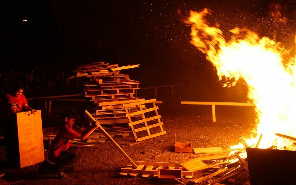 Throwing boards onto the growing bonfire in Ramat Gan. (photo credit: Chen Leopold/Flash 90)