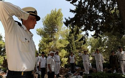 Soldiers and citizens standing near the graves of fallen IDF soldiers as the two-minute-siren marking Memorial Day is sounded across the country, in the military cemetery on Mount Herzl during Memorial Day in 2013 (photo credit: Gili Yaair/Flash90)