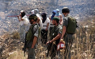 Masked settlers stand alongside IDF soldiers in the West Bank (photo credit: Wagdi Ashtiyeh/Flash90)