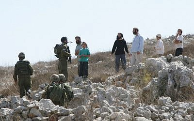 Illustrative: Jewish settlers argue with Israeli soldiers near the West Bank village of Burin, September 21, 2010. (Wagdi Ashtiyeh/Flash90)