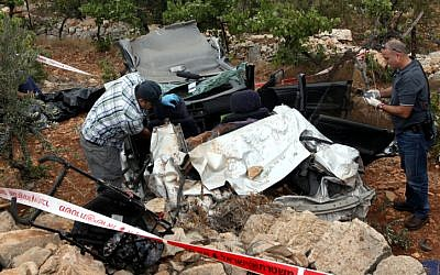 Rescue personnel at the scene where Asher Palmer and his son were killed by rocks thrown at their vehicle on Route 60 near Kiryat Arba in the West Bank on Friday, September 23, 2011. (photo credit: Yossi Zamir/Flash 90)