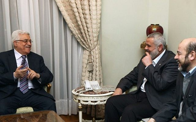 Palestinian Authority President Mahmoud Abbas (left) and Hamas Prime Minister Ismail Haniyeh (center) meeting in Cairo, on February 23, 2012 (photo credit: Mohammed Al-Hums/Flash90)