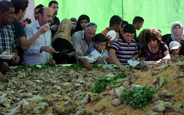Ramallah residents serve themselves from a massive dish with chickpeas, cracked wheat (freekeh) and chicken (photo credit: Issam Rimawi/Flash 90)
